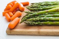 Asparagus and Carrots Close Up on a Wooden Chopping Board stock photos