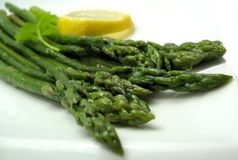Asparagus cooked. Plate of cooked steamed asparagus with lemon and parsley and butter on white Royalty Free Stock Photography