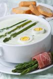 Asparagus cream soup with eggs in white bowl macro Stock Image