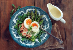 Asparagus with egg. Green asparagus with egg poached, shrimps and fresh salad on the rustic background Royalty Free Stock Images