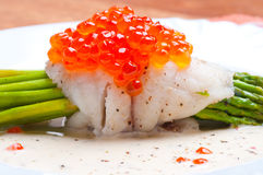 Asparagus with fish and red caviar in creamy sauce Royalty Free Stock Images