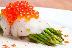 Asparagus with fish and red caviar in creamy sauce Stock Photos