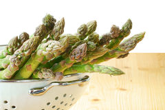 Asparagus fresh from market. Fresh green asparagus in a white enamel colander on a rustic wooden table Stock Images