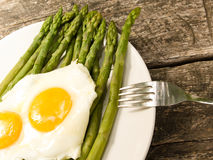 Asparagus and fried egg Stock Images