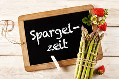Asparagus in German on chalkboard next to spears. Asparagus text written in German on black chalkboard next to spears wrapped in string next to strawberries over stock images