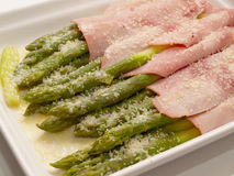 Asparagus with ham & grated cheese. Close-up view of asparagus baked with ham olive oil & grated parmesan cheese Stock Image