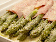 Asparagus with ham & grated cheese 2. Close-up view of asparagus baked with ham olive oil & grated parmesan cheese Royalty Free Stock Images