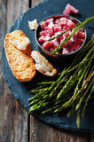 Asparagus with ham on the wooden table Stock Photography