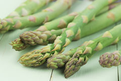 Asparagus heads. Shot of asparagus heads on green background stock photo