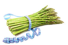 Asparagus and measuring tape on a white background. royalty free stock images