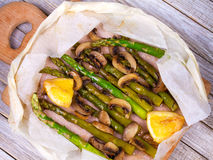 Asparagus, Mushrooms and Lemon in Parchment. View from above, top studio shot. Stock Photos