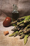 Asparagus and oil. A bunch of fresh asparagus,an isolated and red tomatoe,a bottle of italian oil Royalty Free Stock Images