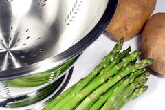 Asparagus, Potatoes and Colander. This is an image of potatoes, asparagus, and a colander royalty free stock photo