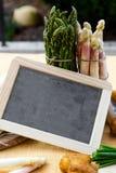 Asparagus, potatoes, empty blackboard Royalty Free Stock Image