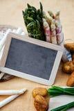 Asparagus, potatoes, empty blackboard Stock Image