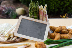 Asparagus, potatoes, empty blackboard Royalty Free Stock Image