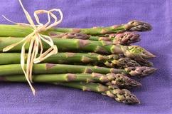Asparagus on purple napkin. Fresh raw asparagus bunch on purple napkin in horizontal format Royalty Free Stock Image
