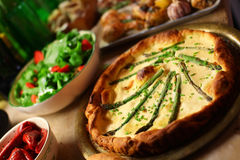 Asparagus quiche with appetizers on the table Royalty Free Stock Image