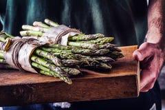 Asparagus. Raw asparagus. Fresh Asparagus.Green Asparagus. Tied asparagus in other positions. Farmer carries tied asparagus. On a wooden board royalty free stock photo