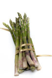 Asparagus with ribbon. A bunch of asparagus, tied with gold ribbon, isolated on white Royalty Free Stock Images
