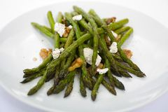 Asparagus Roasted with Walnuts and Goat Cheese. Asparagus roasted in olive oil with goat cheese and crushed walnuts on a white plate. A tastey side dish to any Stock Photo