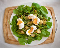 Asparagus salad. With spinach, potatoes and soft-boiled eggs on a chopping board Royalty Free Stock Photos