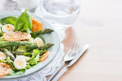 Asparagus Salad with quails eggs and cheese crisps. Asparagus Salad with quails eggs, avocado and cheese crisps, healthy detox lunch Royalty Free Stock Image