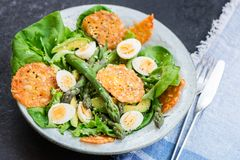 Asparagus Salad with quails eggs and cheese crisps. Asparagus Salad with quails eggs, avocado and cheese crisps, healthy detox lunch Stock Photo