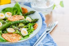 Asparagus Salad with quails eggs and cheese crisps. Asparagus Salad with quails eggs, avocado and cheese crisps, healthy detox lunch Royalty Free Stock Photo