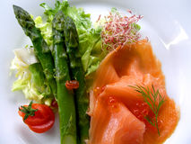 Asparagus with smoked salmon. Smoked salmon with green asparagus on plate ready to serve royalty free stock photos