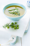 Asparagus soup in a bowl topped with fresh cream, dill and chive Stock Photo
