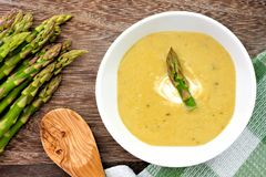 Asparagus soup overhead scene against rustic wood Stock Images