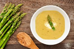 Asparagus soup overhead scene on rustic wood background Stock Photography