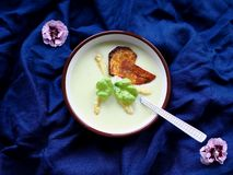 Asparagus soup with potato chip on navy background royalty free stock photo