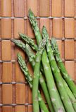 Asparagus Spears. Fresh asparagus spears on wooden tiled kitchen mat royalty free stock photo