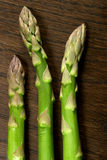 Asparagus Spears on Wood. Three asparagus spears on a wooden background royalty free stock photos