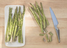 Asparagus Spears, Wooden Board, White Plate, Knife. Royalty Free Stock Images