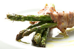 Asparagus starter. Asparagus wrapped in bacon topped with olive oil Stock Images