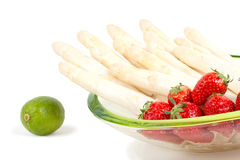 Asparagus with strawberries. In bowl, isolated on white background Stock Photos