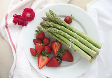 Asparagus with strawberries on plate Royalty Free Stock Image