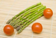 Asparagus and tamatos on bamboo substrate Stock Photo