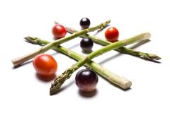 Asparagus tic tac toe. Concept for healthy food games using asparagus and tomatoes to play tic tac toe Royalty Free Stock Photos