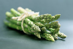 Asparagus. Tied with string on teal background, light from kitchen windows royalty free stock photography