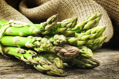 Asparagus. Tied with string on a wooden background stock images