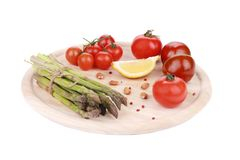 Asparagus and tomatoes on wooden board. Stock Image