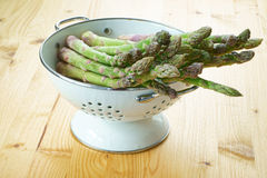 Asparagus in a white enamel colander. Fresh green asparagus in a white enamel colander on a rustic wooden table Royalty Free Stock Images