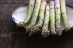 Asparagus on a white plate on the wooden table Stock Photos