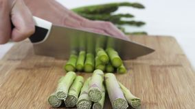 Asparagus. Woman Cuts Asparagus on a Wooden Cutting Board Close Up. Close Up of Asparagus on a Cutting Board on White Background, Woman Hands stock footage