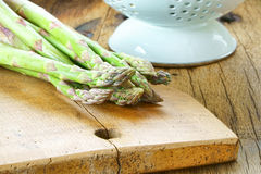 Asparagus on wooden board. Green fresh asparagus on a rustic wooden cutting board Stock Photography