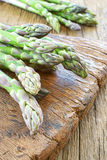 Asparagus on wooden board. Green fresh asparagus on a rustic wooden cutting board Stock Photo